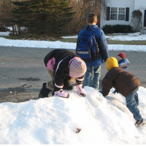 Kids play in snow while waiting for bus